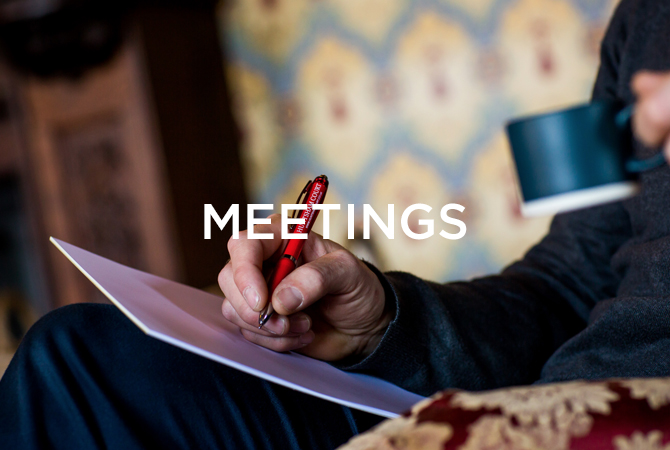 man with notepad and pen making notes with meetings text