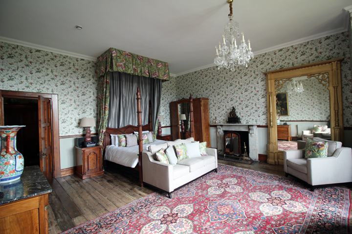 A bedroom at Huntsham Court with four poster bed and sofas