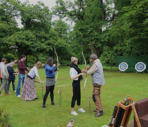 a group of people trying archery in front of targets